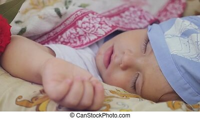 Happy pretty child sleeping at flower outdoors in summer...