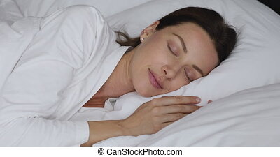 Happy pretty lady sleeping in bed, daydreaming in morning...