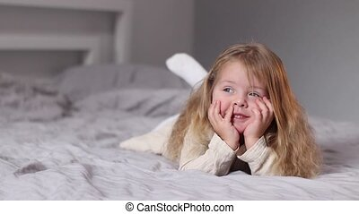 happy pretty little blonde girl in beige dress lying on a bed in gray bedroom. morning routine, childhood, toddler, daughter. Full HD footage.