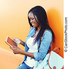 Happy pretty smiling african woman using tablet pc looking on screen in city