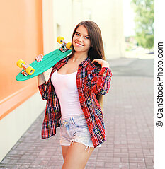 Happy pretty smiling woman with skateboard in city