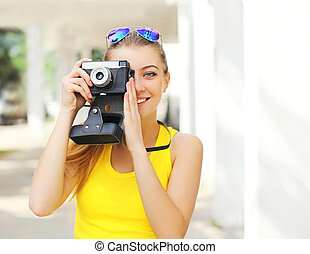 Happy pretty smiling young woman with retro vintage camera in city