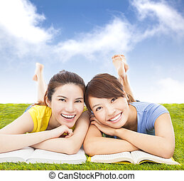 happy pretty students lying on the grassland with books