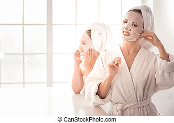 Happy pretty woman caring about her skin