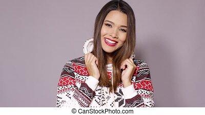 Happy pretty woman in warm winter fashion snuggling into her...