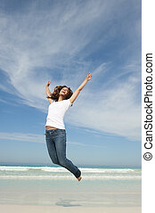 Happy pretty woman jumping for joy at beach