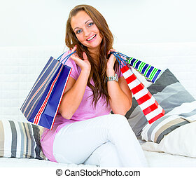 Happy pretty woman sitting on couch at home and holding shopping bags in hands