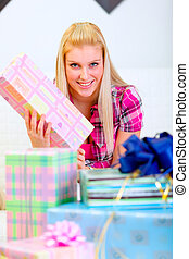 Happy pretty woman sitting on sofa and holding present in hands