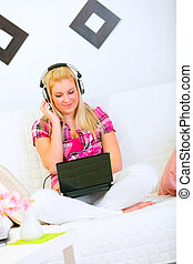 Happy pretty woman sitting on sofa with laptop and listening music in headphones