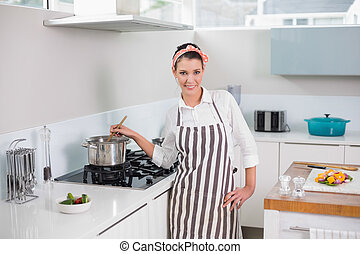 Happy pretty woman with apron cooking