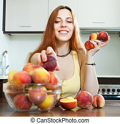 woman with peaches in home kitchen
