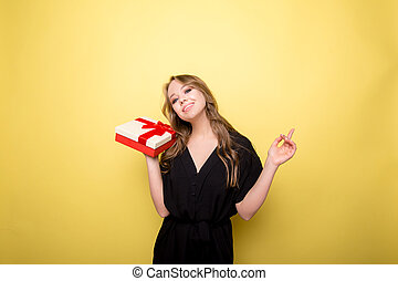 Happy pretty young woman holding gift box