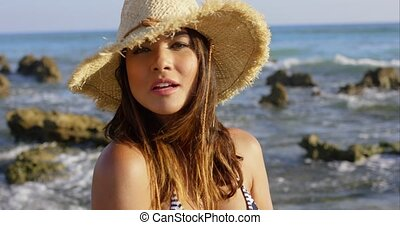 Happy pretty young woman on a rocky seashore