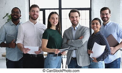 Happy professional multiethnic business team people smiling looking at camera