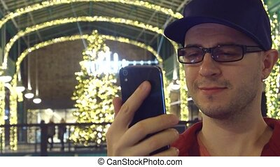 Happy programmer in black rim glasses answering video call on his mobile phone in a Cristmas decorated cafe. 4K video