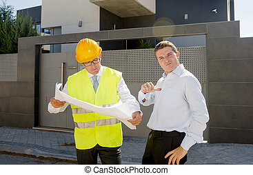 happy proud customer and constructor foreman worker with new house building blueprints in real state business concept