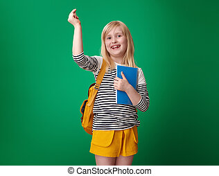 happy pupil snapping with fingers isolated on green