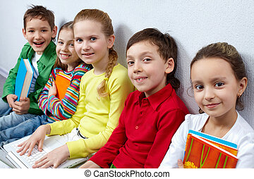 Portrait of five happy pupils looking at camera