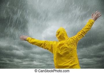 Happy rainy season - man in yellow coat enjoying the rain,...