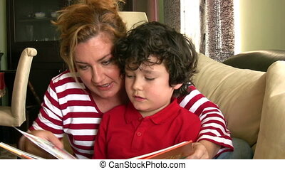 Happy reading - Happy mother and son reading a book sitting...