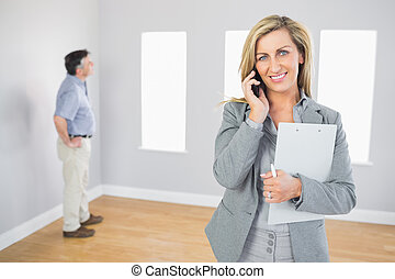Happy realtor calling someone with her mobile phone in empty...