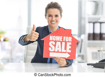 Happy realtor woman showing home for sale sign and thumbs up