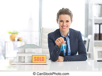Happy realtor woman showing keys