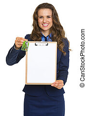 Happy realtor woman with keys showing blank clipboard