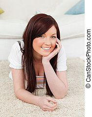 Happy red-haired female posing while lying on a carpet