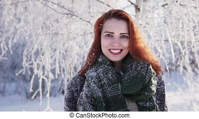Happy red-haired girl smiling against a snow-covered tree in a winter forest