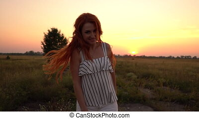 Happy red-haired woman goes to the field at sunset, turns around and looks into the camera