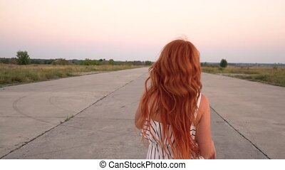 Happy red-haired woman running along the road with flying hair