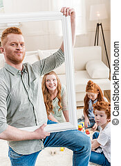 happy redhead family looking through white frame, big family portrait concept