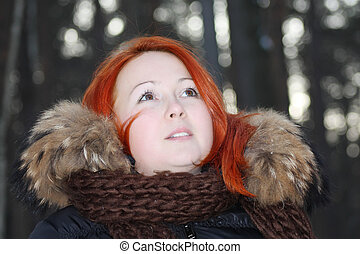 Happy redhead girl in warm clothes looks up in forest at winter.