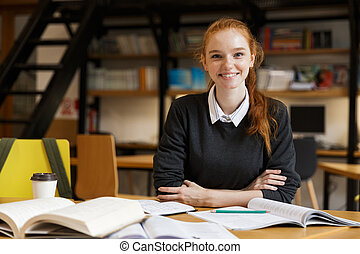 Happy redhead lady student sitting at the table with books in library.