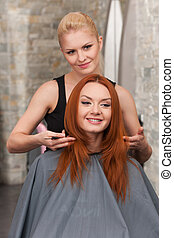 Happy redhead woman getting a new haircut. Beautiful blond hairdresser giving new haircut to female customer at parlor