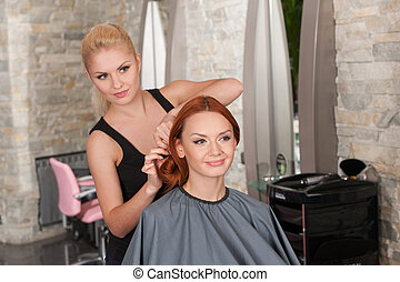 Happy redhead woman getting new haircut. Beautiful blond hairdresser selecting new haircut for female customer at parlor