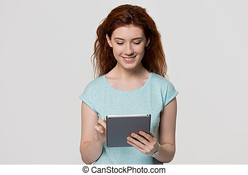 Happy redhead woman using digital tablet isolated on background