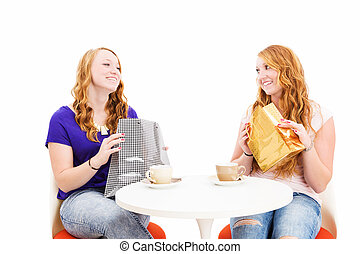 happy redhead women sitting at a coffee table with shopping bags on white background