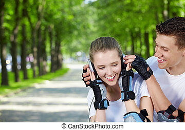 Happy relationship - Young attractive couple with headphones...