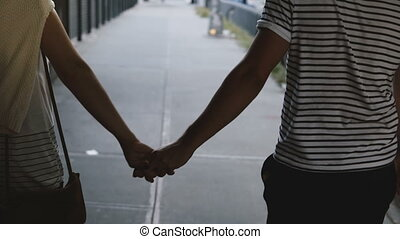 Happy relaxed adult romantic couple walking along evening...