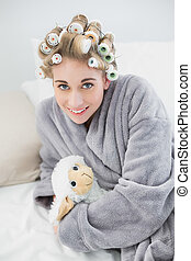 Happy relaxed blonde woman in hair curlers cuddling a plush sheep in a bedroom