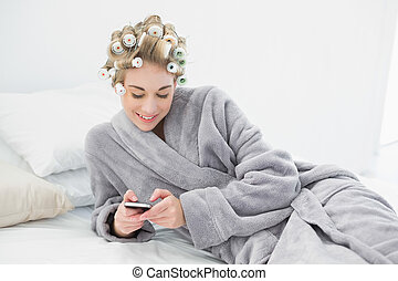 Happy relaxed blonde woman in hair curlers using her mobile...
