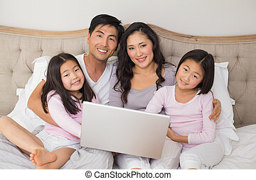 Happy relaxed family of four using laptop in bed