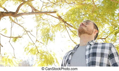 Happy relaxed man breathing fresh air in a park - Happy...