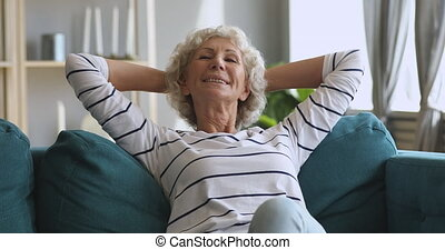 Happy relaxed old woman resting dreaming sitting on comfortable sofa