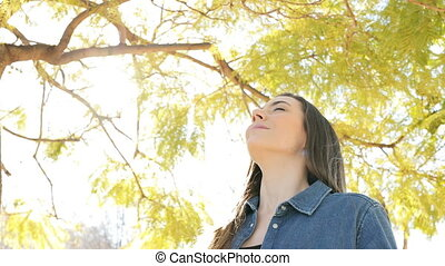 Happy relaxed woman breathing fresh air in a park - Happy...