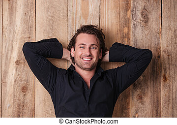 Happy relaxed young man posing with hands behind head