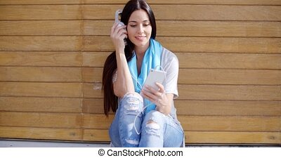 Happy relaxed young woman listening to music on her mobile...