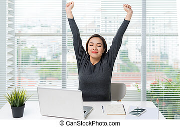 Happy relaxed young woman sitting at her desk with a laptop,...